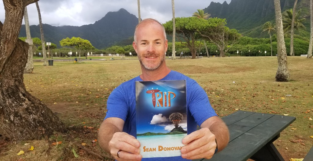 """Sean, posing with a copy of his first novel, """"The Trip""""."""