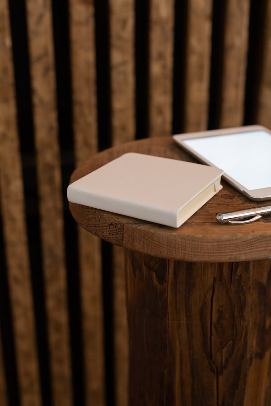 notebook with pen and tablet on table