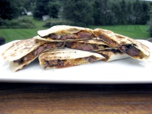Grilled Beef Quesadilla with melted Cheddar Cheese, leek, and Guajillo Pepper Sauce