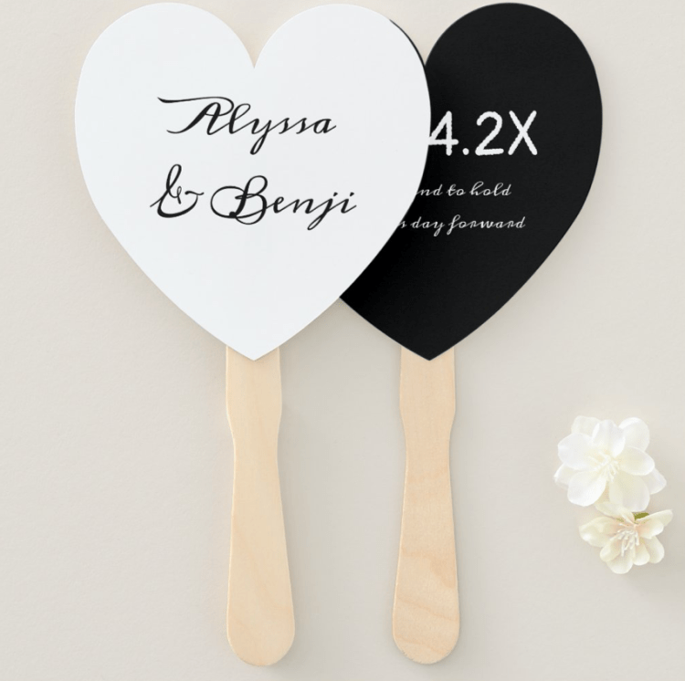 Black and white wedding fan in shape of a heart with names on one side and date with saying on the other.