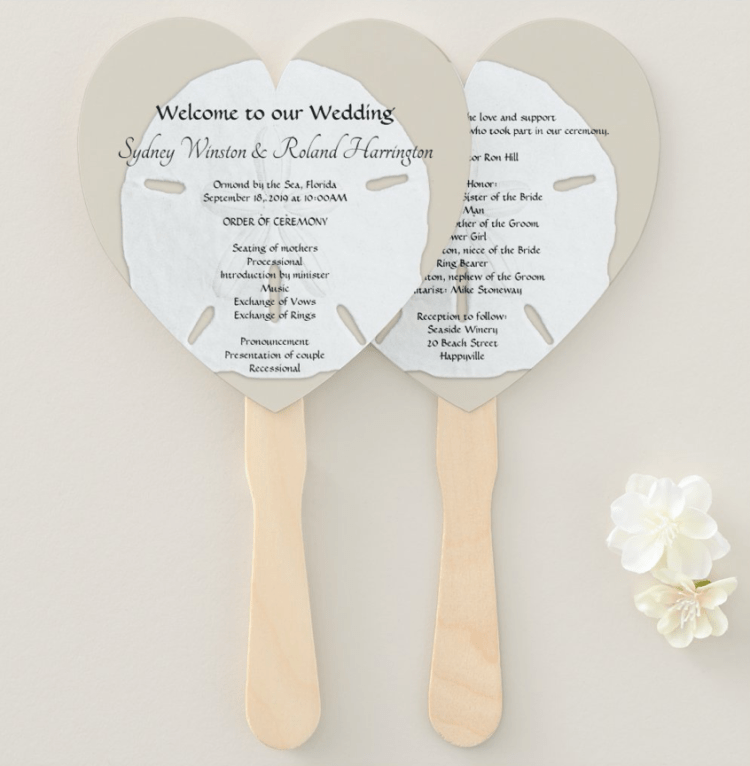 Heart shaped wedding program fans with big sand dollar as the background for text.