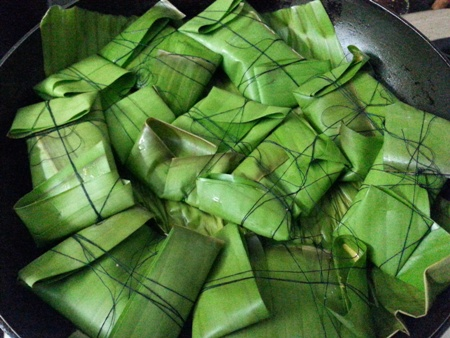 Place banana leaf wrapped fish parcels in a frying pan for Bhetki recipe