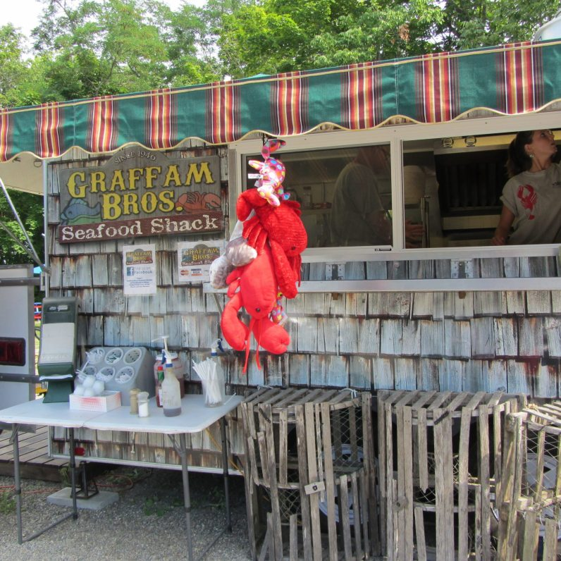 Old lobster traps and a red stuffed lobster adorn this seafood shack.