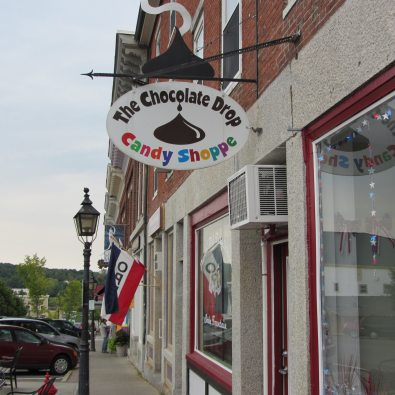Brick building with a sign which is a picture of a chocolate drop.