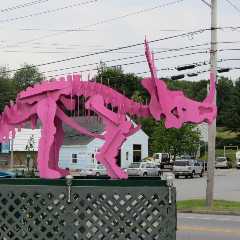 Bright pink dinosaur on a green pedestal.