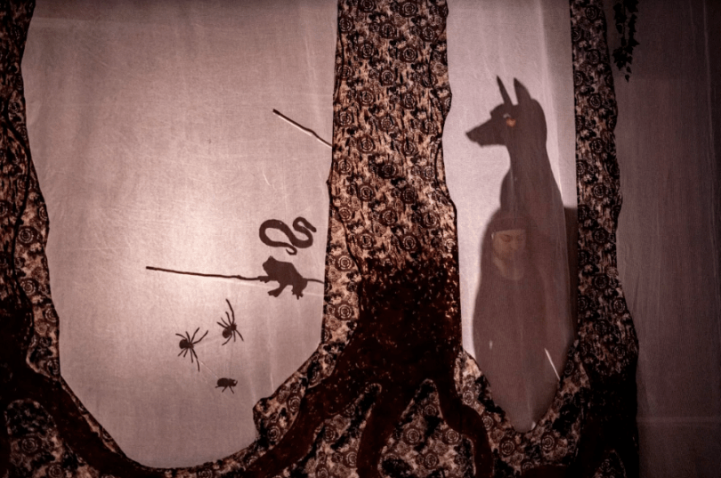 A series of shadow puppets on a scrim with tree trunks. A large dog, a snake, a toad, spiders, and a beetle.