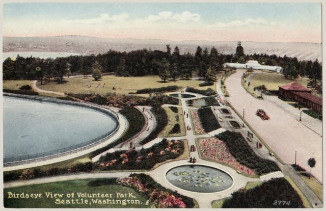 Color-rendered photo providing aerial view of round lily ponds connected by straight path. Curving edge of reservoir is seen to the left, and a drive leading to a glass building (conservatory) in the distance is on the right.