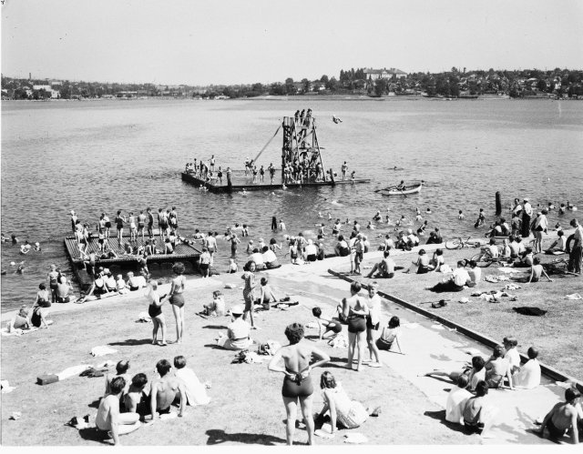 Aerial black and white photo of grassy shoreline crowded with sunbathers and swimmers in the water and on floats. A high dive is on one float. The lake's far shore and neighborhood beyond can be seen in the background.