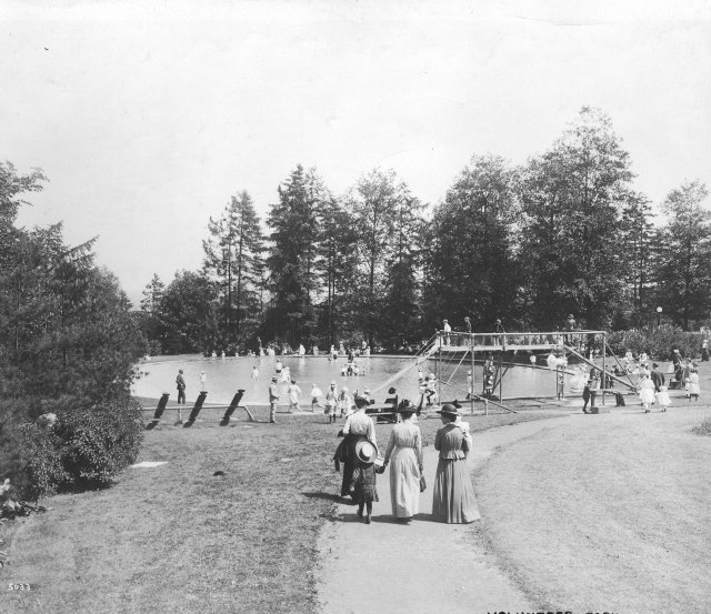 Black and white photo with three women and a girl walking away from the camera along a curving path surrounded by lawn, toward a large circular wading pool with a long slide. Several children are in and around the pool and on the slide platform. Dress is early 20th-century.