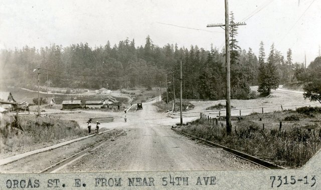 black and white photo looking down graded but unpaved street to low buildings and treed slope in distance