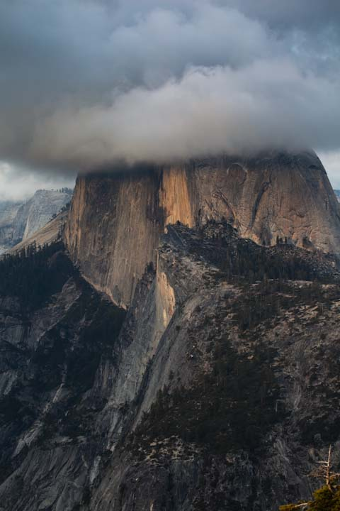 Half Dome sitting among the clouds around sunset