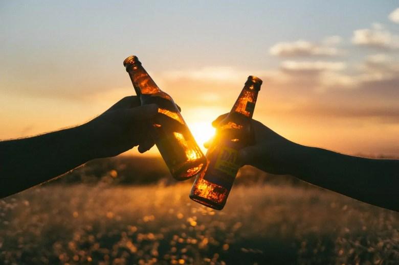Deux mains qui tiennent une bière et qui trinquent devant le coucher du soleil