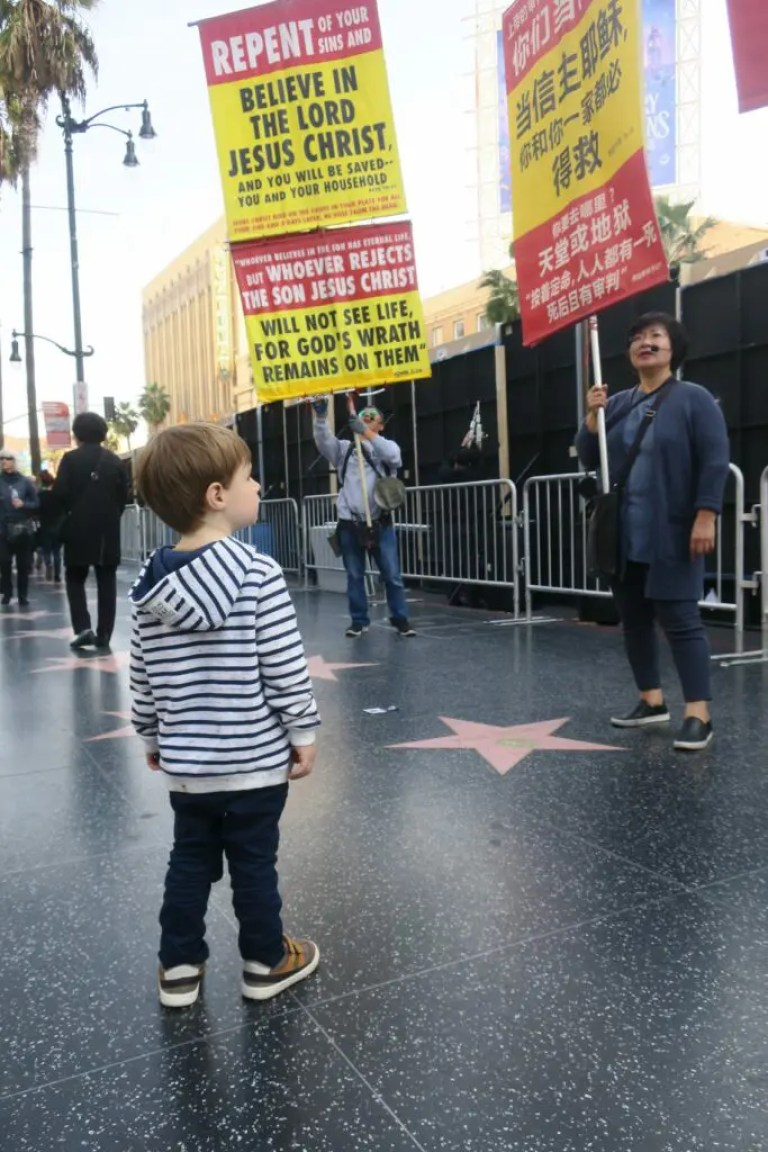 Enfant sur Hollywood Boulevard devant des manifestants Belive in the lord.