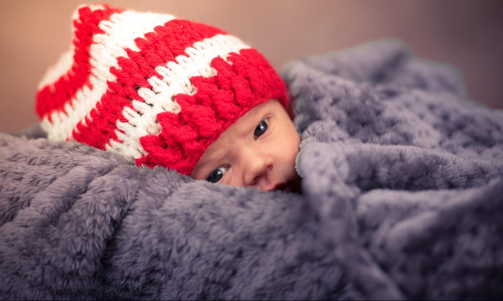 bébé avec un bonnet emmitouflé dans une couverture