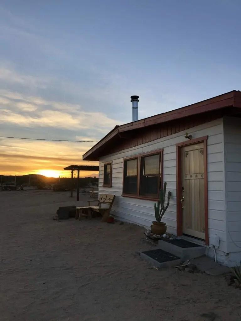 Maison au Joshua Tree et soleil couchant