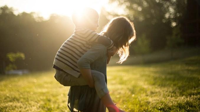 Un garçon sur le dos d'une fille dans le soleil couchant - Enfants
