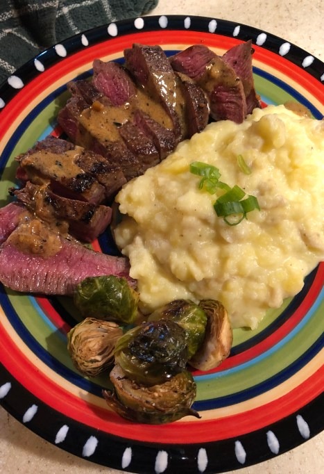 A fiesta plate with roasted brussel sprouts, mashed potatoes, and steak.