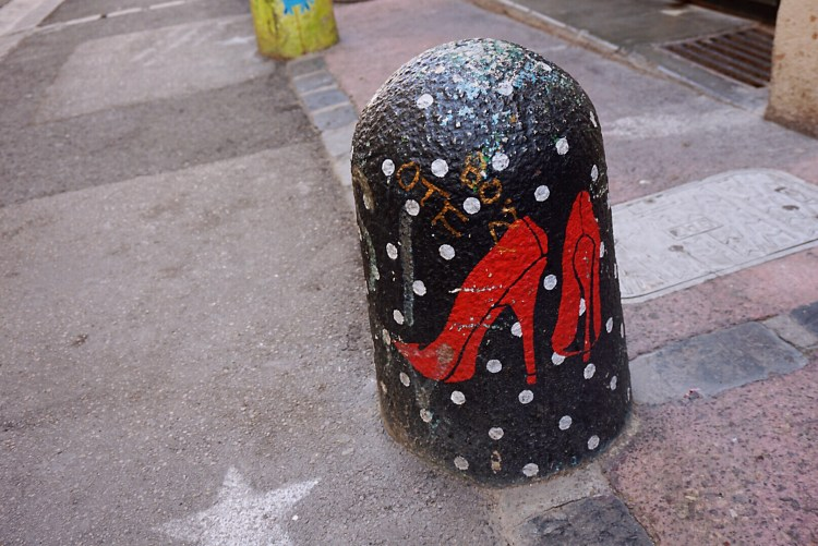 Red shoes decorated bollards - Street art Montpellier