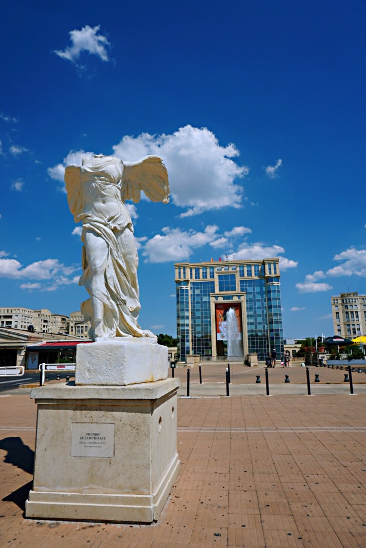 Greek statue with a building in the background - Visit Occitanie