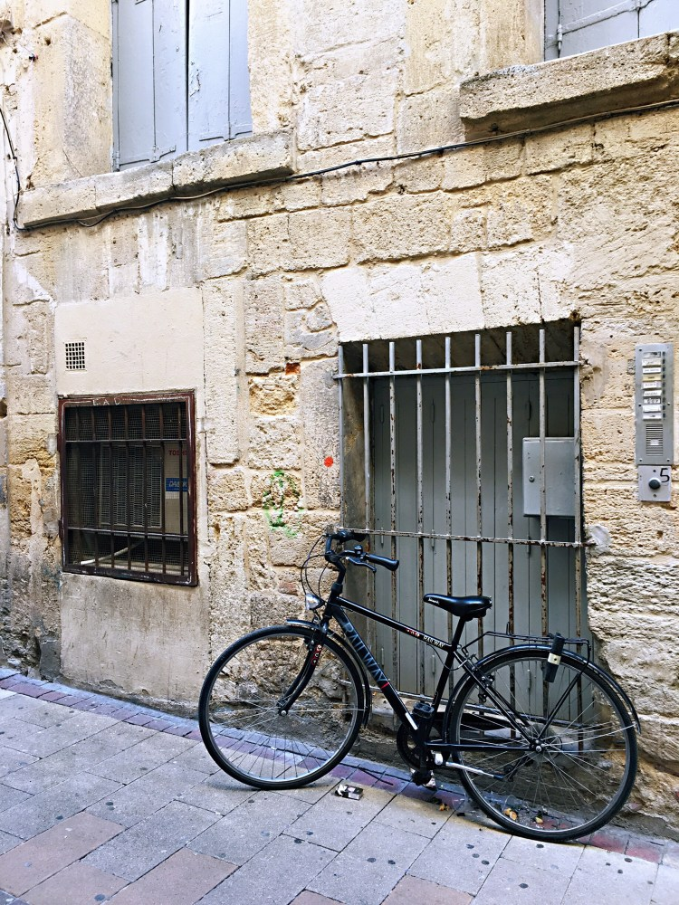 Black bike outside a grey door with fence - Visit Occitanie