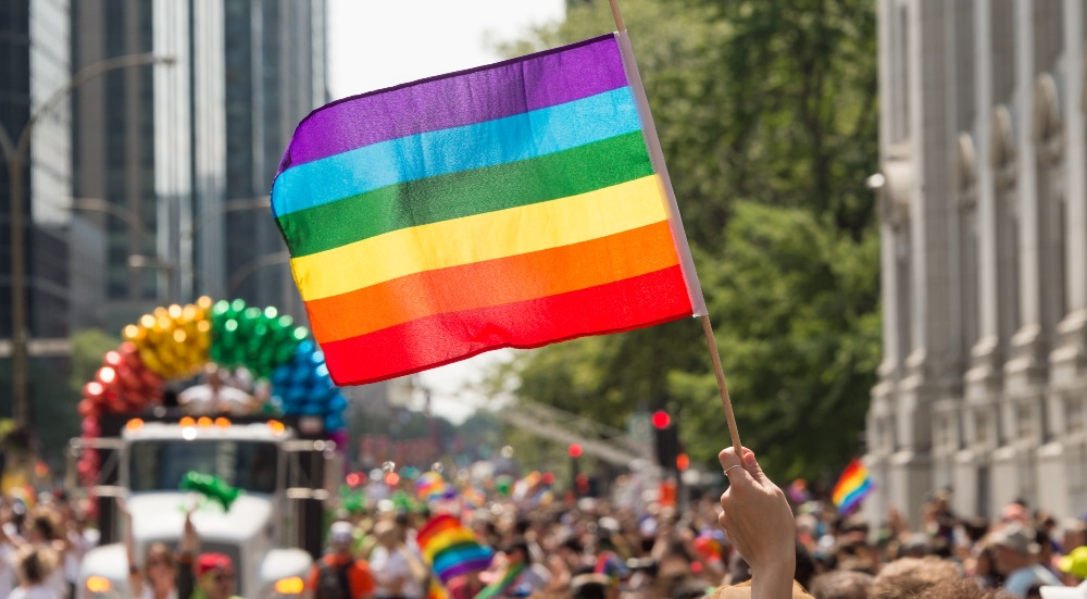 Montreal, CANADA - 20 August 2017: Gay rainbow flag at Montreal gay pride parade with blurred participants in the background