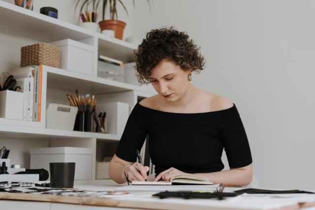 focused designer drawing sketch in notebook