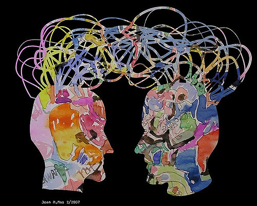 """A watercolor illustration showing two profile heads with a jumble of """"wires"""" connecting them."""