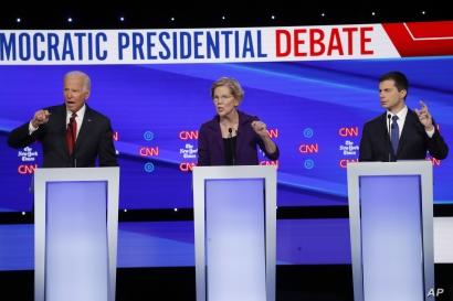 Democratic presidential candidate former Vice President Joe Biden, left, Sen. Elizabeth Warren, D-Mass., center and South Bend…