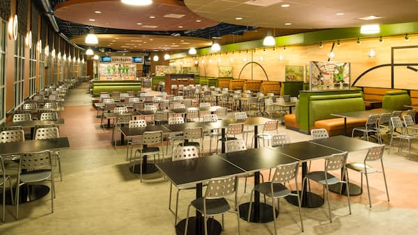 A dining area featuring modern decor, tables, chairs, booths, artwork and overhead lighting