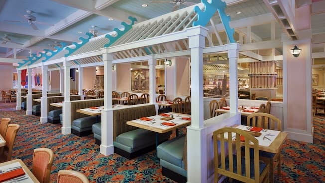 Bright and airy dining room with blue booths and birch wood tables and chairs at Cape May Cafe