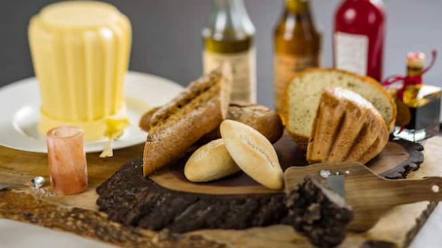 French baguette, brioche and multi grain bread served together on a wooden plate