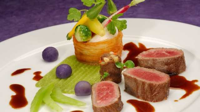 Slices of rare lamb artistically plated with miniature vegetables on a layer of celery puree