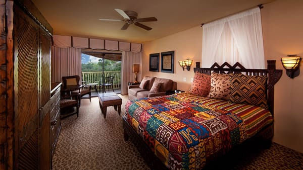 A Bedroom With Sofa Bed And Sliding Glass Doors Leading To Balcony