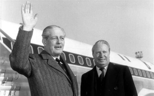 Harold Macmillan waves to unseen observers as he stands before a jet airliner with future Prime Minister Edward Heath in 1963
