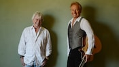 Band members from Air Supply standing side-by-side against a wall as one of them holds a guitar