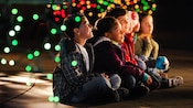 Dots of colorful lights swirl around wide-eyed children sitting crossed-legged