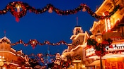 An ornament shaped like a treble clef hangs on a Christmas tree with lights