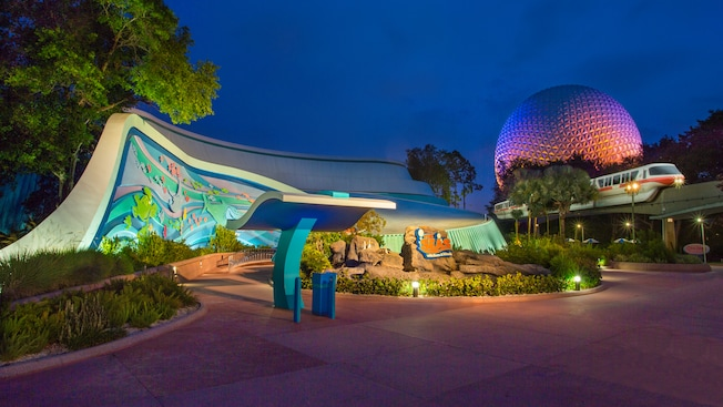 The Seas with Nemo & Friends Pavilion lit up at night, next to a monorail train and Spaceship Earth