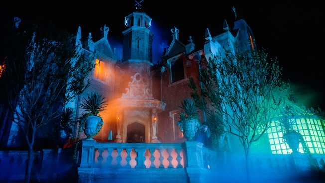 Spooky bluish glow of the exterior of the Haunted Mansion at night