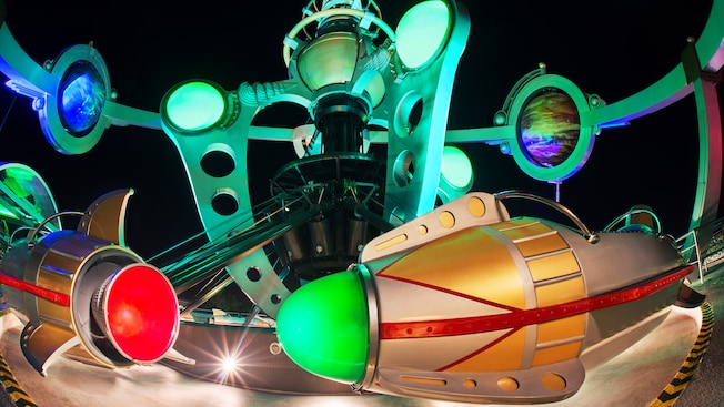Rocket ships on the Astro Orbiter attraction lit up at night in Magic Kingdom park