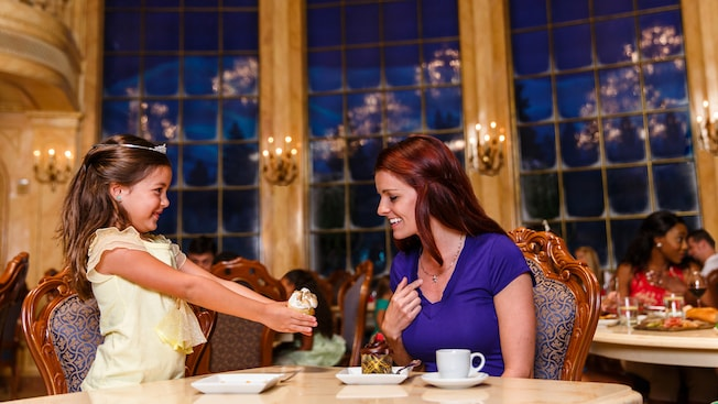 A little girl dressed as a princess shows off a dessert to her mother at a dining table