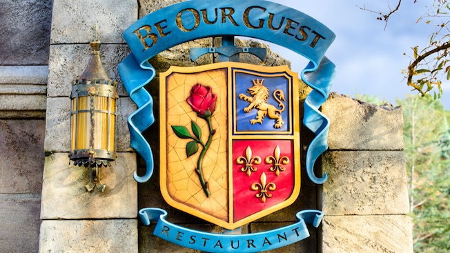 The coat-of-arms signage outside Be Our Guest restaurant