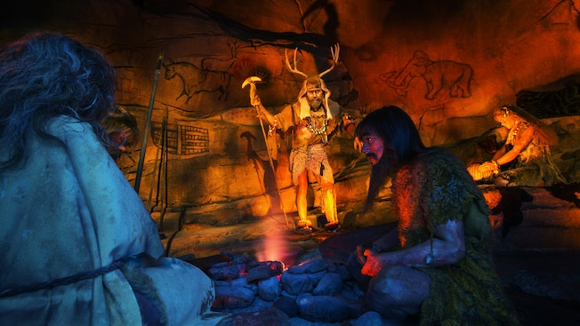 A scene of cavemen and cave paintings in the Spaceship Earth attraction