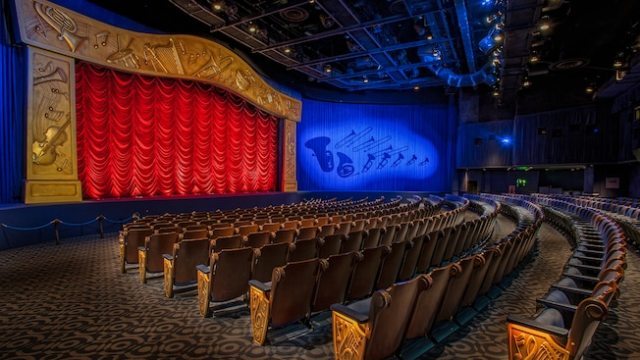 Inside a concert hall with rows of theater seats and a curtained screen at Mickey's PhilharMagic