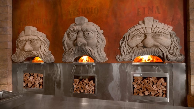 Three wood-fired ovens with comical faces whose mouths show the oven flames
