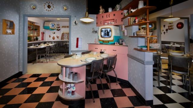 "A pink-and-black kitchenette area with a ""TV Table"" for 4 next to a 1950's-style TV set"