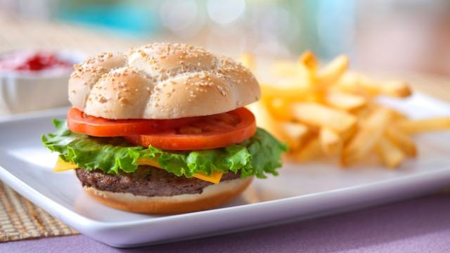 A cheeseburger on a sesame seed bun, topped with tomatoes and lettuce, and served with French fries
