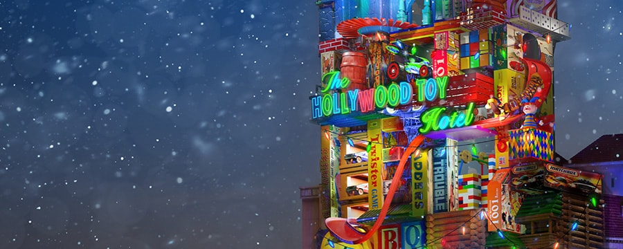 The Hollywood Toy Hotel lit up with lights near trees and falling snow