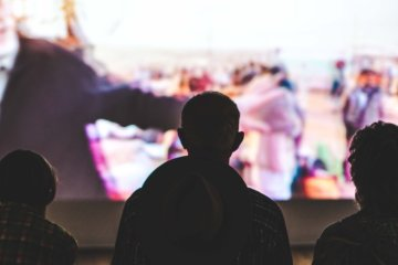 Silhouettes of people watching images on a big screen
