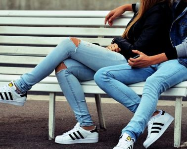 boy and girl sitting on a bench in matching outfits